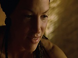 Jolene Blalock seen topless while lying atop a guy in bed,