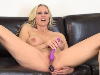 busty julia ann spreads her long legs and sticks a dildo in each hole