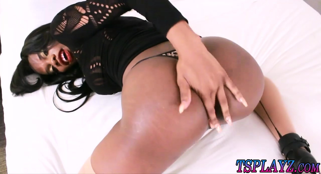 Busty black shemale masturbates her hard cock on the bed