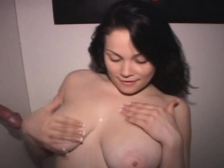 brunette taking cumshot on great big tits through glory hole